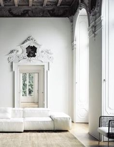 white walls, molding, exposed beams, wood floor, sofa