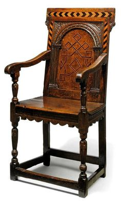 A LATE ELIZABETHAN OAK AND INLAID ARMCHAIR  LATE 16TH CENTURY, YORKSHIRE.  The back panel inlaid with geometric marquetry below a carved arch and chequer inlaid toprail and uprights, with scroll seat rails, fluted underarm supports and fluted tapering legs joined by square stretchers