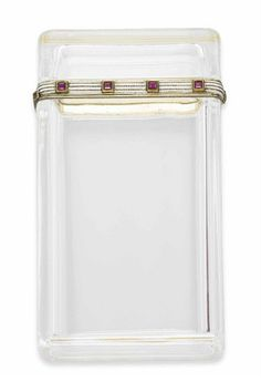 A ROCK CRYSTAL, RUBY AND ENAMEL CIGARETTE CASE, BY FABERGÉ   The rectangular rock crystal case with hinged opening edged with a gold line of white enamel, enhanced by calibré-cut ruby collets, 1912, 9.0 x 5.0 x 2.0 cm  Signed Fabergé (Cyrillic), with workmaster's mark H.W for Henrik Wigström, scratched inventory number 22602