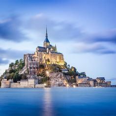 Mont Saint Michel in Normandy, France - a medieval abbey and surrounding walled town that is periodically completely cut off from land by water and is made accessible at low tide