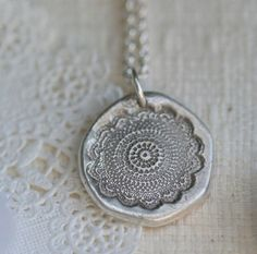 take clay, imprint some pretty charm onto it, paint silver