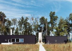 """A lakeside retreat on Madeline Island, Wisconsin, consists of a bifurcated cabin centered on a plinth. Dubbed """"Two Black Sheds"""" (for obvious reasons), the unique island getaway sits low amidst the surrounding four and half acres of forest.  Photo by Chad Holder.   This originally appeared in Off the Beaten Path."""