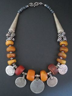 Necklace; antique fossil amber from Morocco, combined with traditional Moroccan Berber spiral pendant with 4 silver coin pendants on either side. Moroccan zebra shells, two large Ethiopian coin silver coins, old cornerless cube Tuareg silver beads and striped Venetian 'Gooseberry' beads of the African trade period. Sterling silver clasp by Luda Hunter