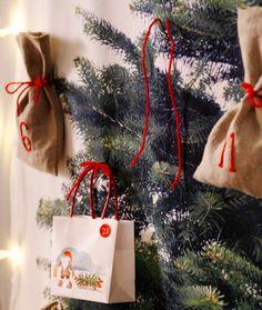 Nahaufnahme von VINTERMYS Geschenktüten und Stoffbeuteln, die an VINTER 2014 Meterware mit Weihnachtsbaummotiv hängen