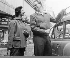 En man och en kvinna klädda i jacka och byxa, står vid en bil. Fotograf: Sten Didrik Bellander, ca 1950-1955