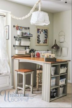 Love this craft room with open storage - high top table with gift wrap paper holder at the end on the wall.