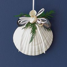 "Coastal Winter 4"" white scallop shell holiday tree ornament sprinkled with greenery, shells and and white ribbon."