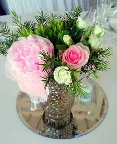 Elige un centro de mesa con espejo y cristal para darle un aire fresco y ligero a la decoración de tu boda. El color verde aporta naturaleza y los tonos de rosa y blanco el romanticismo. #centrodemesa #centrosboda #centrosconespejo #rosas #peonias.