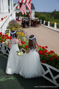 cute flower girls at Grand Hotel Porch Wedding overlooking the horse carriages, flags, and geraniums with flowers and tiara by Margaret's Garden and hair by Astor's Salon photo by Paul Retherford on Mackinac island, Northern Michigan