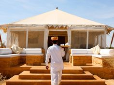 A waiter delivers afternoon tea to one of the tented suites at the Serai, in Desert National Park, Jaisalmer.