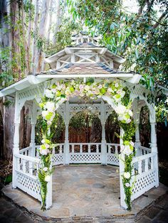 Romantic outdoor wedding space with a gazebo-decorated arch