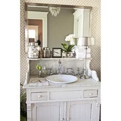 vintage cabinet made into bathroom vanity with marble top and shelf. upscale shabby and romantic look