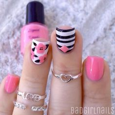 A really cute looking pink nail art design. Using white as base coat, cute pink flowers are drawn on top. Black polish is also used for the stripes as well as the leaves of the flowers.