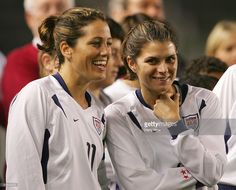 Julie Foudy #11 of USA and MIa Hamm #9 of USA smile before the game against Mexico during the 'Fan Celebration Tour' finale on December 8, 2004 at The Home Depot Center in Carson, California.