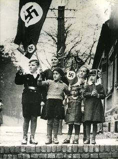 This picture is of multiple young children shown holding the Nazi flag. It represents the Nazi Youth, and how Germans had unflinching resolve for their leader, and his views.