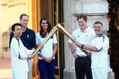 Prince William, Duke of Cambridge, Catherine, Duchess of Cambridge and Prince Harry watch Wai-Ming hand over the London 2012 Olympic Torch to John Hulse during a visit to Buckingham Palace during Day 69 of the London 2012 Olympic Torch Relay on July 26, 2012 in London, England. The Olympic flame is making its way through the capital on the penultimate day of its journey around the UK before arriving in the Olympic Stadium on Friday evening for the Olympic games' Opening Ceremony.