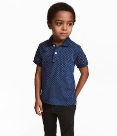 Dark blue/dotted. Short-sleeved polo shirt in cotton piqué with a ribbed collar. Short button placket, embroidery detail on chest, and short slits at sides