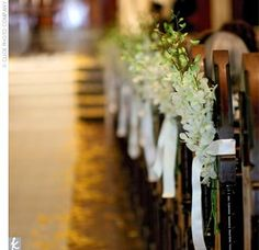 flowers on the end of a pew bench....would be stunning on the back of a chair too