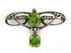 Art Nouveau piece with 20 eight-cut Diamonds set in Sterling Silver and backed with Gold and two large Peridots set in Gold.