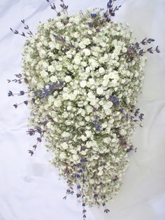 a beautifully designed teardrop shaped bouquet made with gypsophila, and a splash of lavender