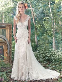 Maggie Sottero - TAMI, A stunning illusion back and feminine illusion sweetheart neckline, edged in floral lace appliqués, takes center stage in this Vogue satin A-line slip dress with lace and tulle overlay. Finished with covered buttons over zipper closure.