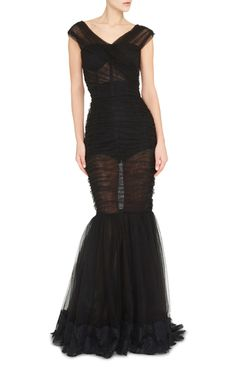 This **Dolce & Gabanna** dress elicits romance with its formfitting cut flaring out to a mermaid skirt. Its finished in a sheet fabrication with a feminine lace along the hem.