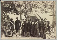 A group photo of Co. A 8th NY Militia soldiers outside their camp, with a dog.