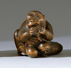 "WOOD NETSUKE Contemporary By Shinzan Masanao. In the form of a seated monkey eating peaches. Inlaid eyes. Signed ""Masanao Shinzan""."