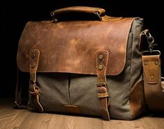 """Size: L:13.5"""" H: 11"""" W:4"""" Exterior: Two large side-by-side pockets shrouded by a genuine leather flap-over, secured and accented with brass buckles and rivets. Interior: Small brass zipper pocket, lig"""