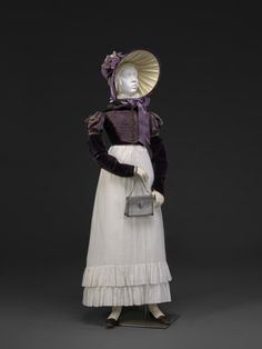 """Velvet and silk twill Spencer, 1818-20; windowpane check muslin skirt (no bodice but straps over shoulders); reproduction bonnet by Lydia Fast; steel """"Berlin Iron"""" purse, c. 1790-1810, made in France; From """"An Agreeable Tyrant:... agreeabletyrant.dar.org"""