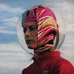 1964 Airline Stewardess wearing Space Bubble Bonnet - Braniff International Airlines enlisted Italian designer Emilio Pucci to add a touch of glamour & weirdness to its service. Stewardesses complained that they couldn't hear passengers speaking.Braniff claimed its purpose was to protect the hair of the stewardesses from wind and rain.