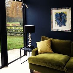 Moss Green velvet sofa against a midnight blue wall. So lush.
