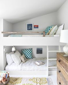 Simple and Understated:  Built-in bunk beds in the daughters' shared room reinforce this Maine home's understated rustic vibe. The simple, streamlined bunks and ladder, for example, balance the reclaimed driftwood railing and dresser made from old barnwood.