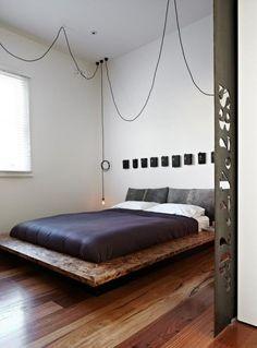 裸電球のペンダントライトが天井からぶら下がるベッドルーム