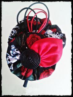 Tocado Diadema forrada en tono negro con dibujo de calaveras y flores rojas, con detalles rojos de inspiración vintage. Pieza única, hecha a mano.