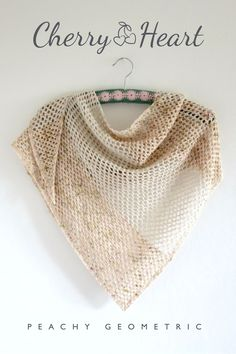 Peach Geometric Crochet Shawl Pattern: Clean lines and geometric textures emphasise the subtle yarns in this loose and flowing asymmetrical triangular shawl.