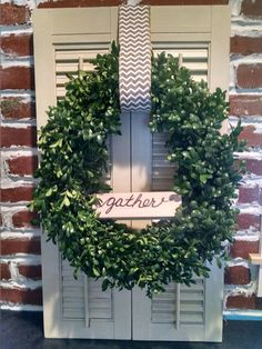 Large boxwood wreath with shutters and wooden gather