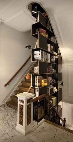 two sided book case squeezed into the space between flights of stairs
