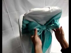 Tying a bow on your chair cover for your wedding reception. Gala Linen has beautiful chair covers and sashes in all colors and fabrics.