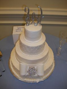 4 tiered wedding cake, bow with brooch.