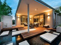 terrasse en bois couverte avec pas japonais et piscine tout autour de la maison