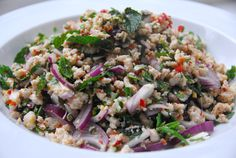 Larb - Thai ground meat salad with cilantro, lemongrass, peanuts, onions, lemon, chilies, and rice powder, garnished with lettuce or leafy veggies.