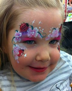 Face painting little lady bug with flowers