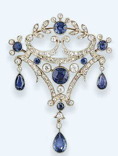 A belle epoque sapphire and diamond brooch   The kite-shaped openwork panel set with brilliant-cut diamond scrolls and millegrain-set sapphire accents and central motif, suspending pear-shaped sapphire triple drops, circa 1905, detachable brooch fitting