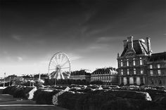 A lovely black and white depiction of a quiet part of Paris where fun and  games can be seen through a towering ferris wheel.  www.bobridgesgallery.com