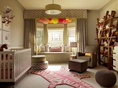 Jeffers Design Group    Adorable girl's nursery design with gray walls paint color, white modern crib, Jonathan Adler pink zebra rug, white  gray round zigzag chevron ottoman, taupe gray glider with ottoman, drum pendant, built-in window seat, white  gray moorish tiles curtains with cornice board valance, pom poms, pink yellow gray pillows and wood bookshelf.