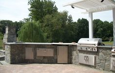American Outdoor Grill Island with Arbor and Nearby Matching Fireplace