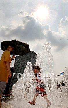무더위가 절정을 이뤄 서울에 첫 폭염경보가 내려진 1일 오후 햇빛이 내리쬐는 서울 시청앞광장 분수대에서 어머니와 아이가 물놀이를 하고 있다.