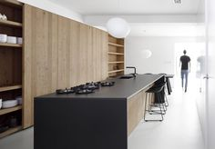 In this minimal Amsterdam kitchen, warm oak is paired with a sleek,black stone countertop for an interesting visual contrast.  Courtesy of: Ewout Huibers