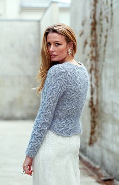 Named after the beautiful Russian ballerina Irina Baronova, a fitted pullover with elegant cables swooning across it in panels with garter stitch dividers for shaping. Timeless, knitted in the round from the bottom up to the armholes then flat to soft square neckline and shoulders. The sleeves are also knitted in the round, long to adorn the hands and set-in. A divine sky blue color, and luscious texture was made by combining Rowan Felted Tweed with Rowan Kidsilk Haze.